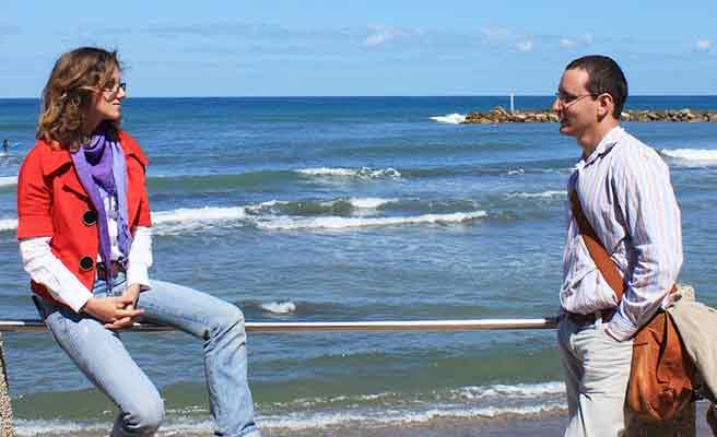 海辺の歩道で語らう男女