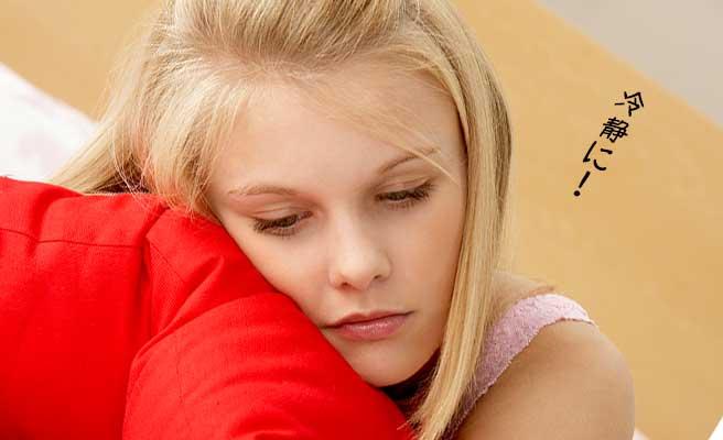 枕を抱いて落ち込む女性