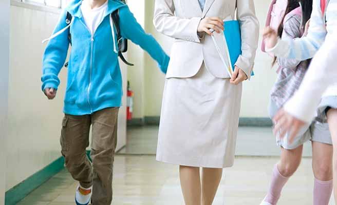 学校の廊下を歩く教師と小学生