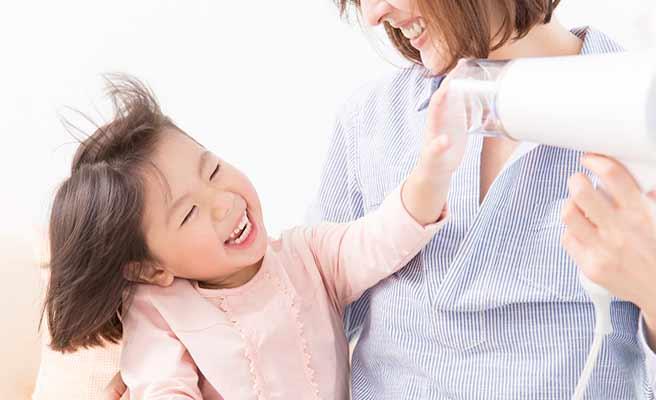 ドライヤーで子供の髪を乾かす母親