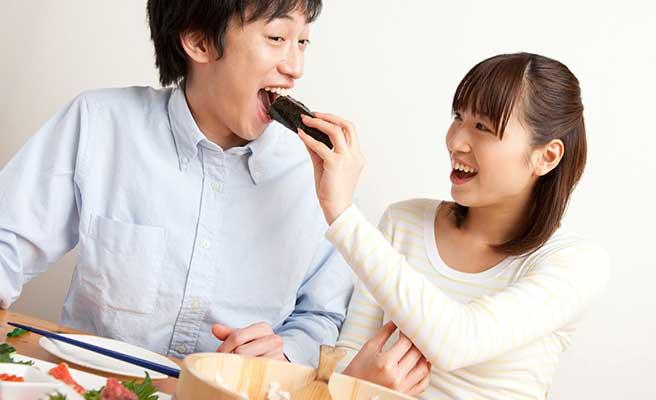 手作り海苔巻きを彼氏に食べさせる女性