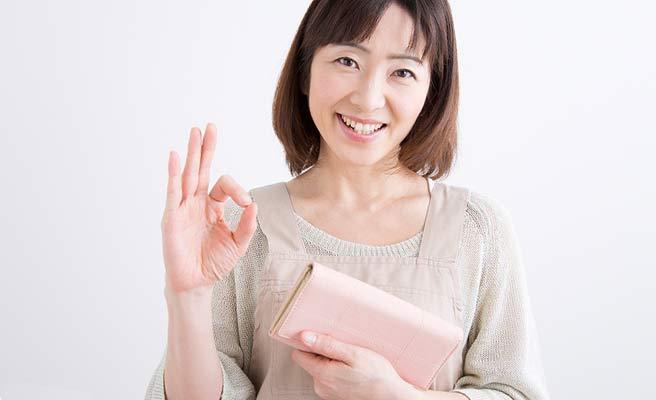 財布を持ちながら指でOKサインを出す女性