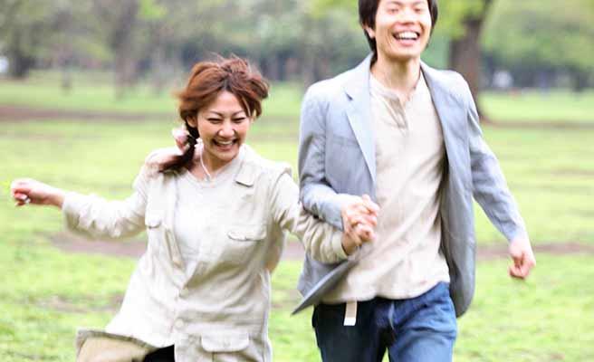 男性と一緒に公園を走る女性
