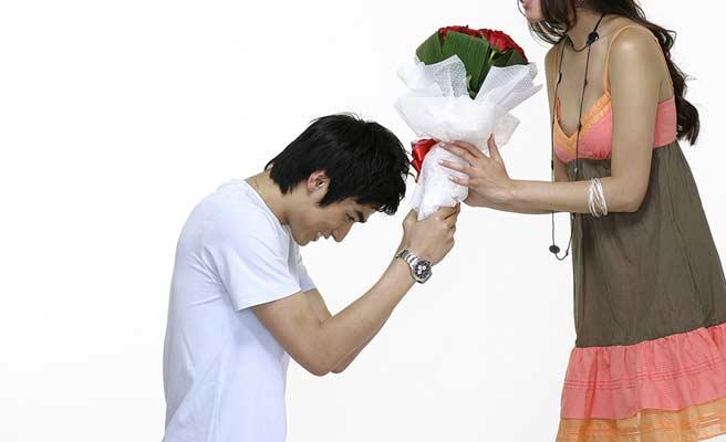女性の前に跪いて花束を差し出す男性