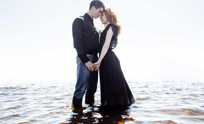 水辺に立って抱擁する男女
