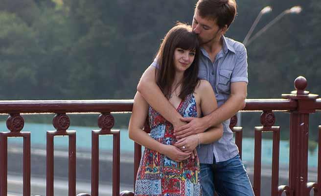 橋の上で彼女を後ろから抱く男性