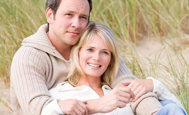 後ろから彼女を抱きかかえる男性と、彼の胸に寄りかかる女性
