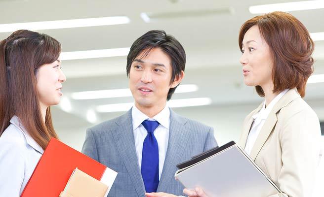 社内で女性達と会話する男性社員