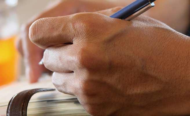 手帳にメモを書く男性の手