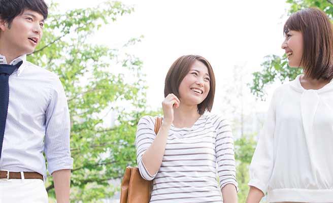歩きながら笑顔で会話する男女