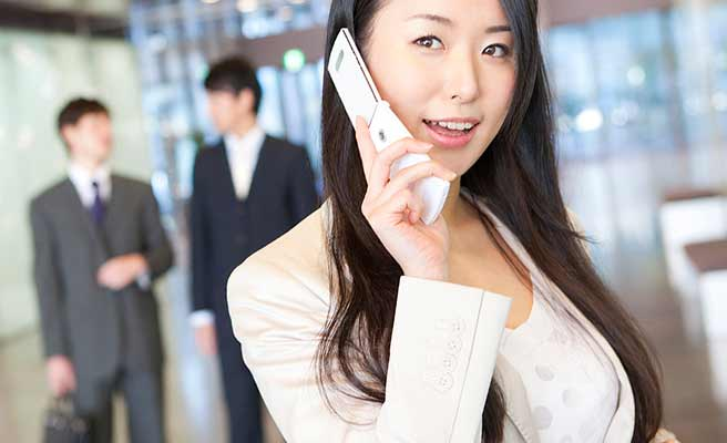 職場で携帯で連絡する女性