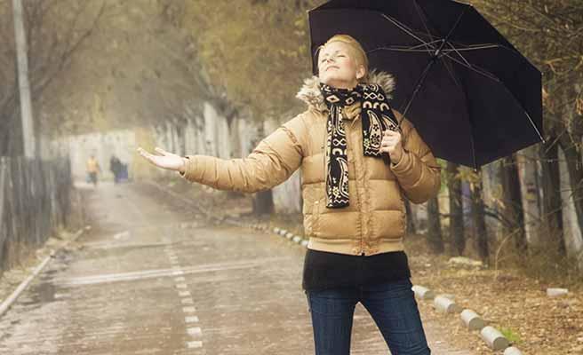雨に手を差し出す女性