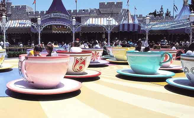 遊園地のカップ乗り物で遊ぶ人々