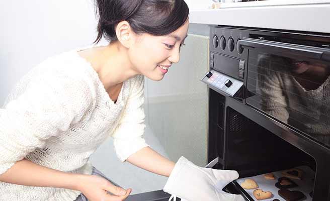 オーブンでクッキーを焼く女性