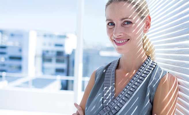 オフィスの窓の日よけの前に立つ笑顔の女性