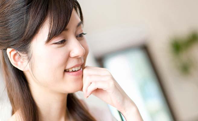笑顔で顎を触る女性