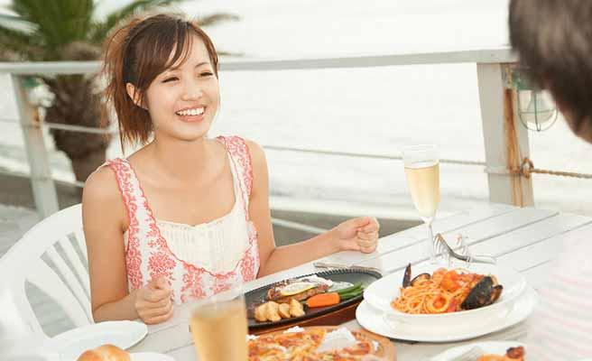 海辺のレストランで食事するカップル