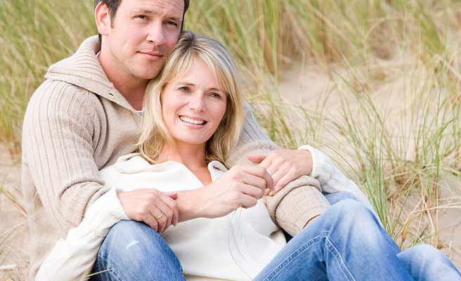 地面に座り込んで妻を胸で支える夫