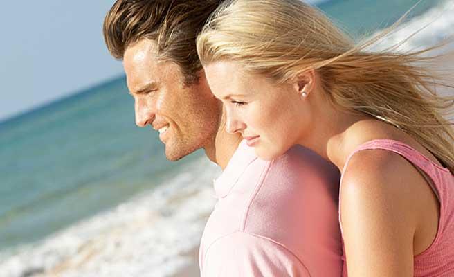 男性の背中に抱きついて同じ方向を見る女性