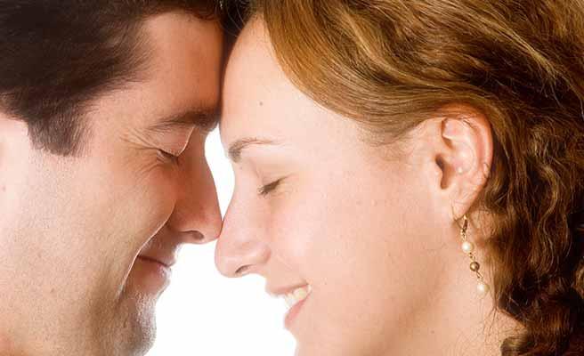男性と額をつけて微笑む女性
