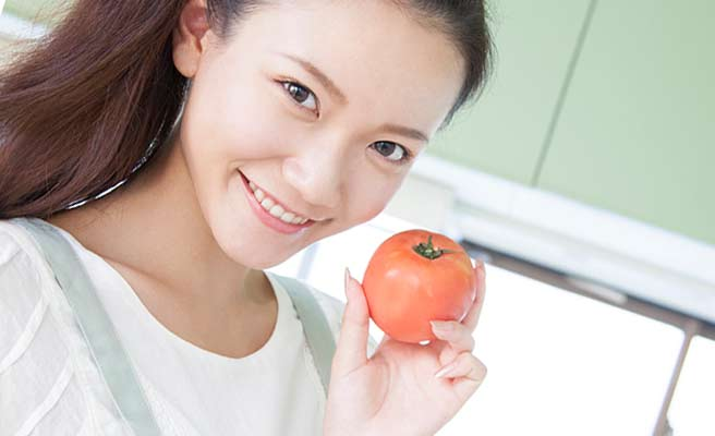 台所でトマトを持つ女性