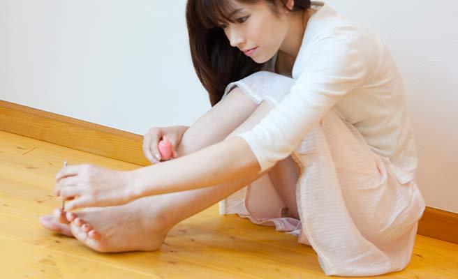 足の指にマニュキアを塗る女性