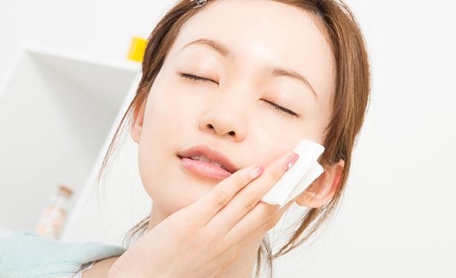 頬に化粧水を塗る女性