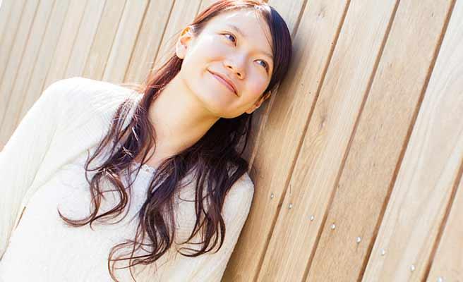 塀に寄りかかって微笑む女性