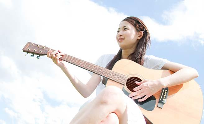 ギターの弾き語りをする女性