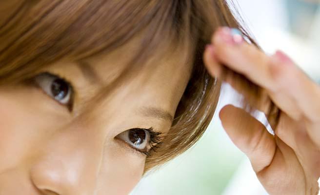 前髪を指で摘みながら見つめる女性