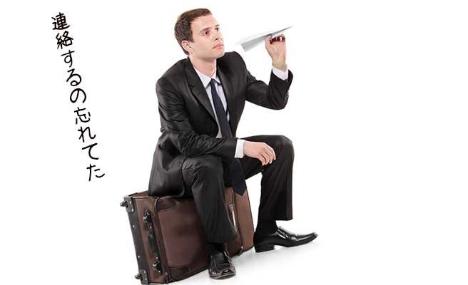 鞄の上に腰掛けて紙飛行機を飛ばす男性