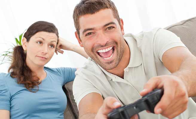 ゲームに夢中な男性を見つめる女子