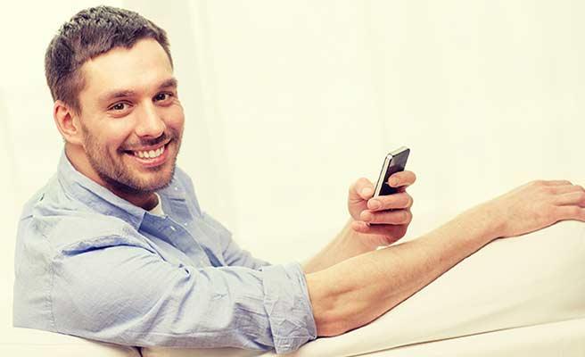 スマホを持ちながら笑顔の男性