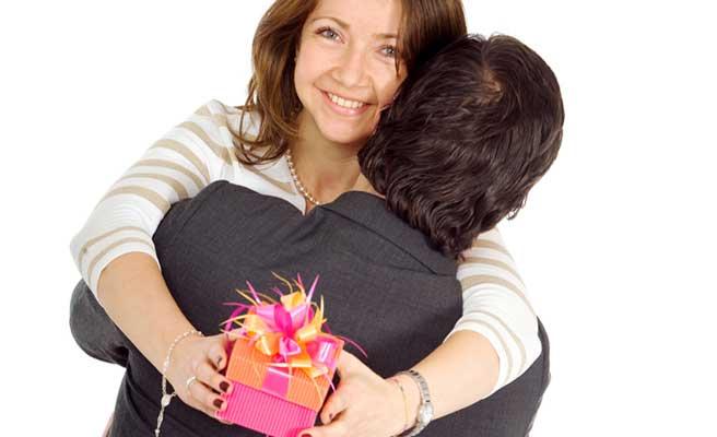 プレゼントを手に彼氏に抱きつく女性