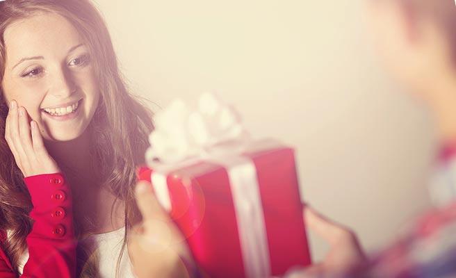 彼氏から贈り物を差し出されて驚く女性