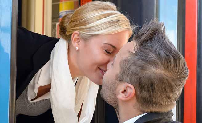 汽車の乗降口で別れのキスをする男女
