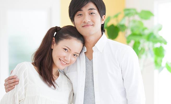彼氏に肩を抱かれて微笑む女性