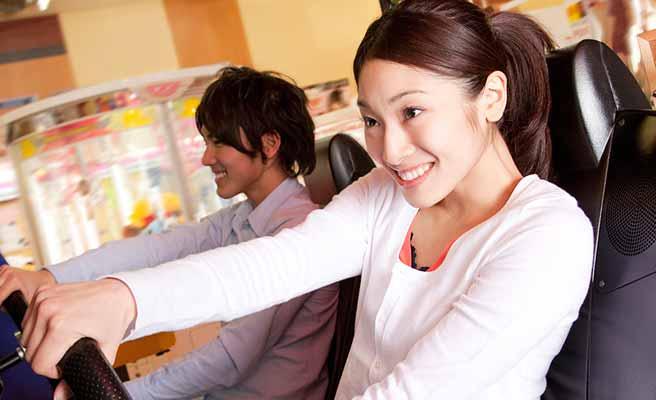彼と一緒にゲームマシンで遊ぶ女性