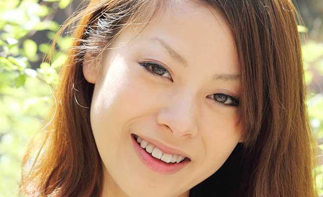 戸外で光を浴びて微笑む若い女性