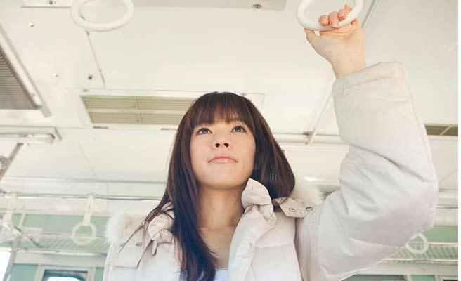 電車内でつり革につかまって立つ女性