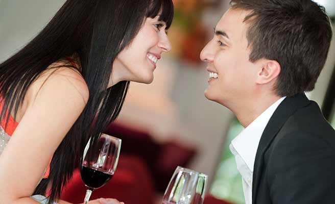 ワインを飲みながら男性に顔を近づける女性