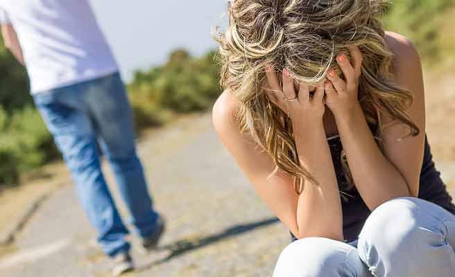 歩き去る彼氏の傍で顔を覆う女性