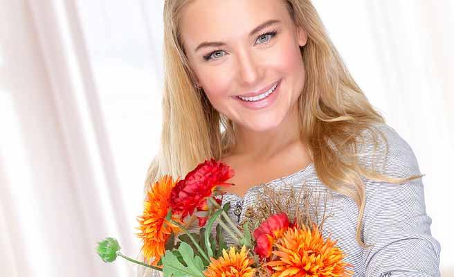 胸に花束を抱いて微笑む女性