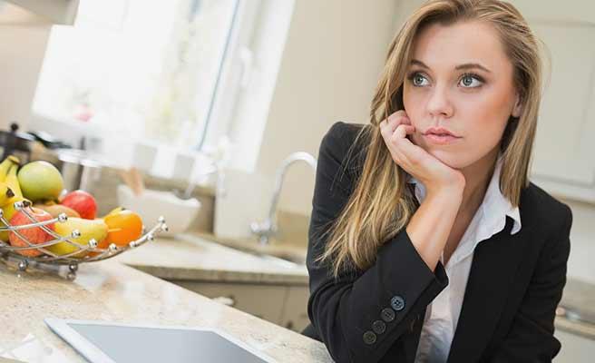 台所のカウンターで頬杖を付いて考える女性