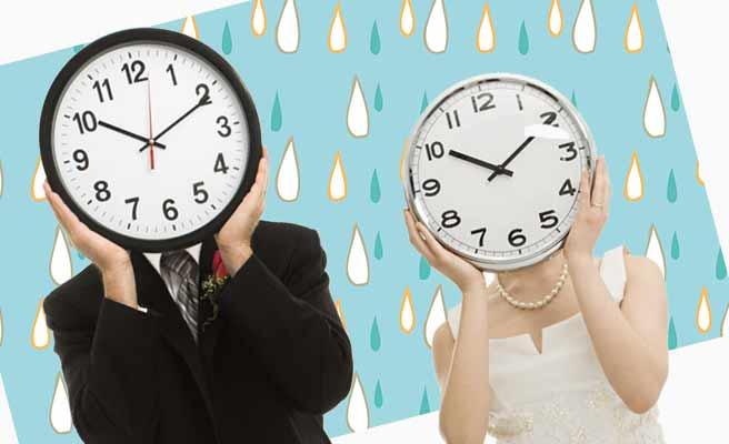 雨の中、時計を気にする男女