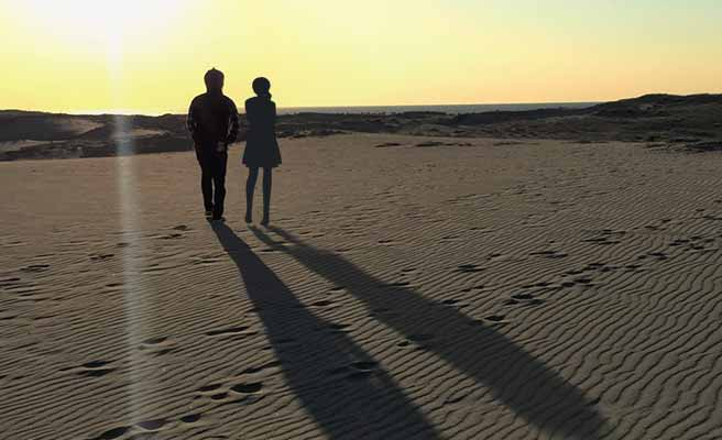 夕暮れの砂浜に並ぶカップル