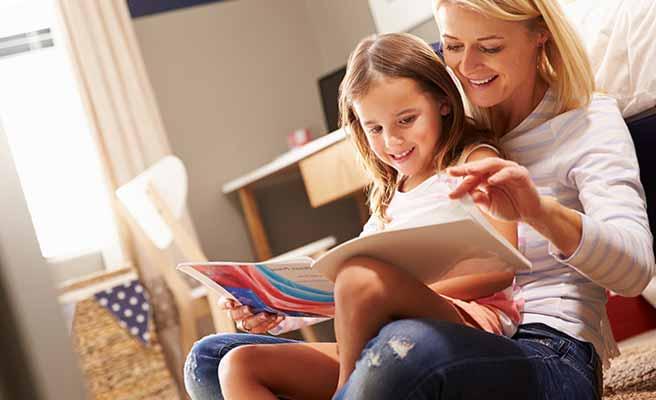 子供を抱きながらノートをめくる母親