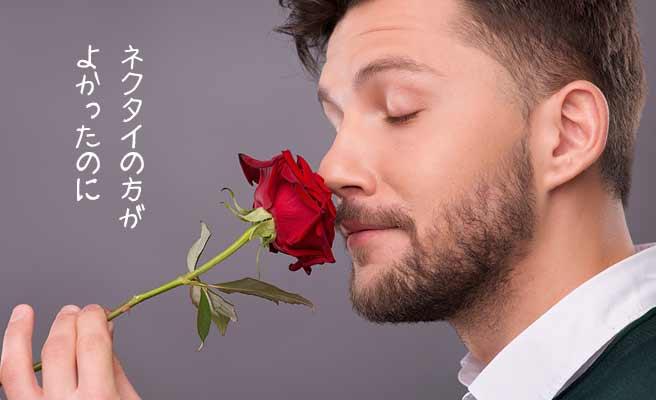 バラの花一輪を自分の鼻先に押し付ける男性