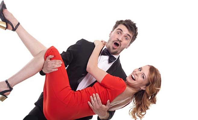 タキシードの男性がドレス姿の女性を抱きかかえている