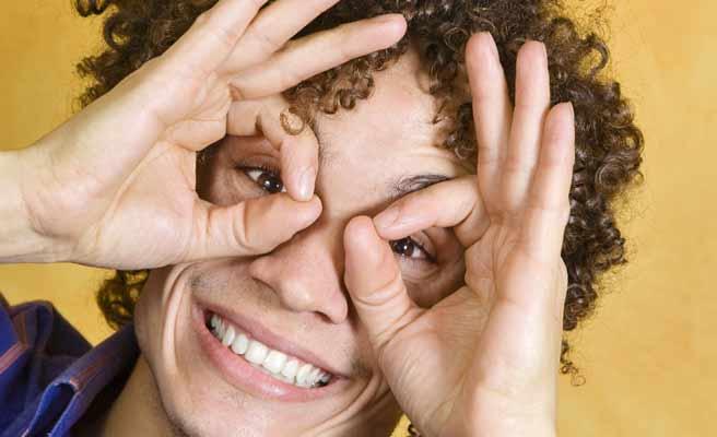 指で眼鏡をつくる男性